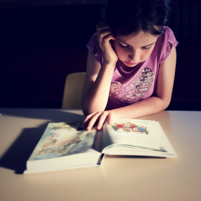 """Young girl absorbed in reading a storybook"" stock image"