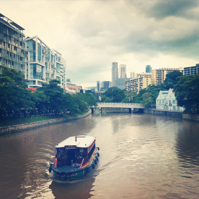 """""""A boat plowing the rivers of Singapore"""" stock image"""