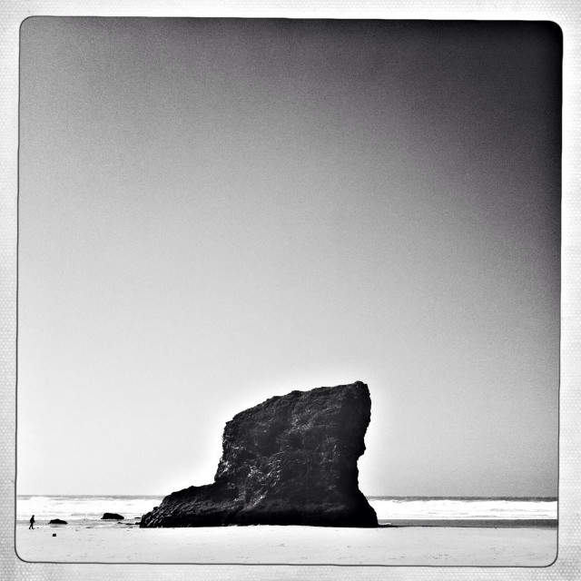 """Rock on beach at Bedruthan Steps, Cornwall with a single figure walking"" stock image"