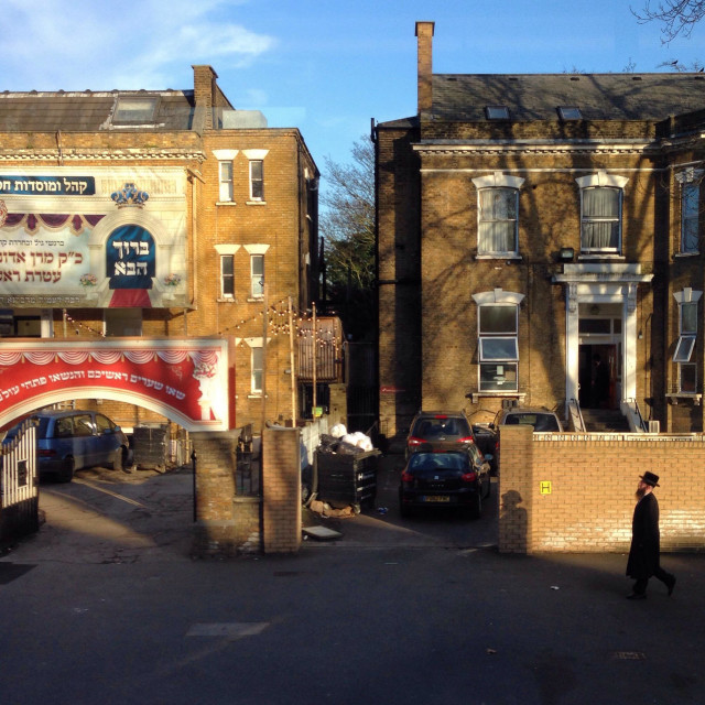 """""""A man walks towards Wiznitz Synagogue in Stamford hill, London"""" stock image"""