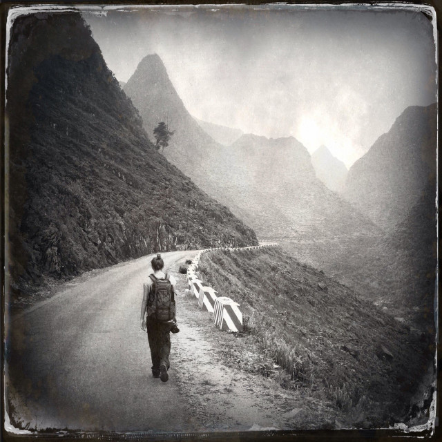"""Backpacker hikes on a road among karst mountains near the ma pi leng pass, Dong Van, Ha Giang, vietnam"" stock image"