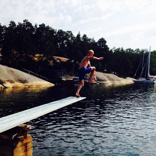 """Blonde boy jumps off diving board in summer in swedish archipelago"" stock image"