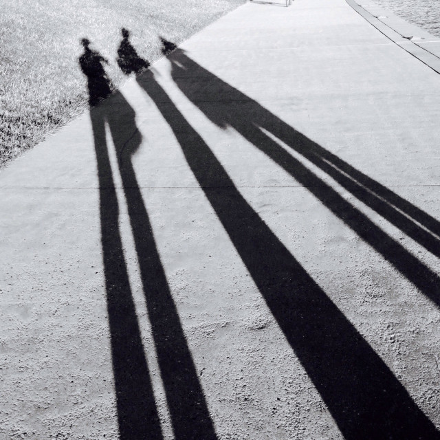 """Long Black & White shadows of 3 people"" stock image"
