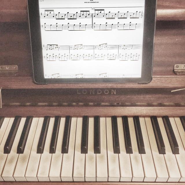 """Using an iPad to learn piano"" stock image"