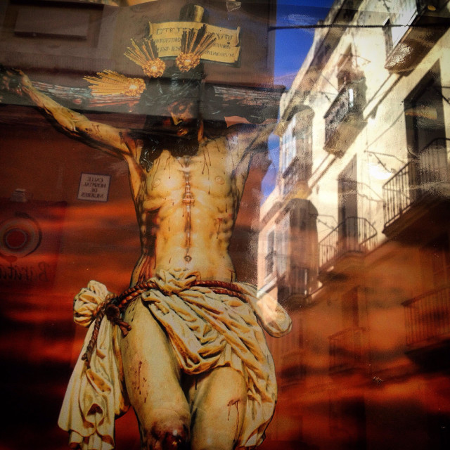 """""""Image of Jesus Christ crucified decorates a window for Easter Week with the reflection of a street of Cadiz, Andalusia, Spain"""" stock image"""