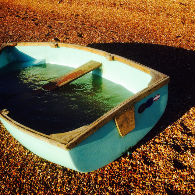 """Dingy full of water on beach beside the river Deben, Bawdsey Ferry, Suffolk UK."" stock image"