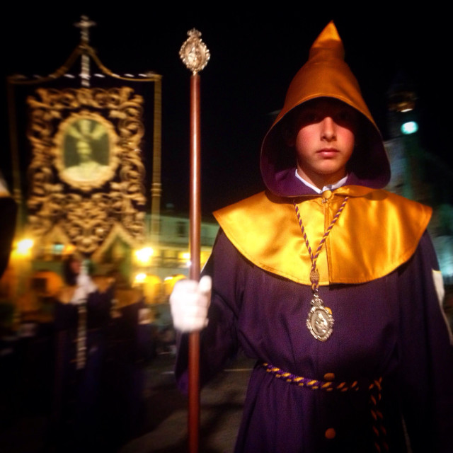 """""""A penitent holding a staff an wearing a pointed hat participates in a procession in Trujillo, Extremadura, Spain"""" stock image"""