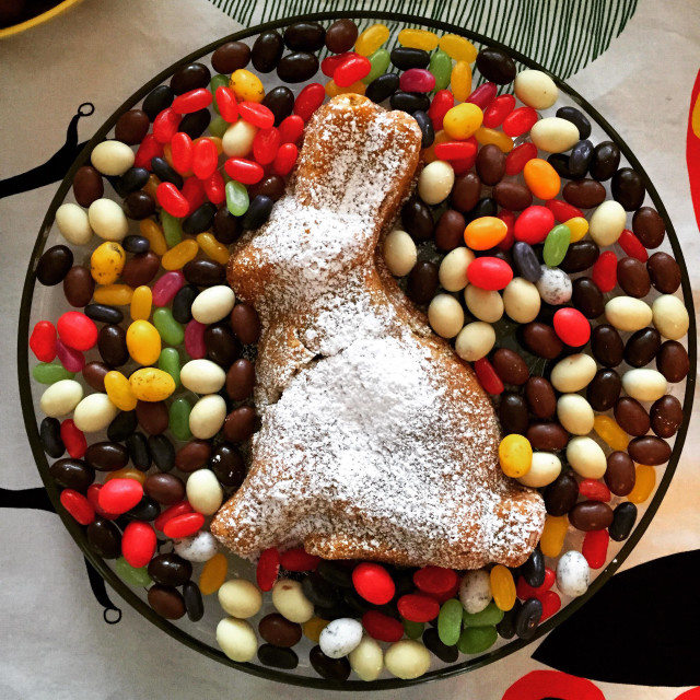 """A home made Easter cake in the shape of a bunny rabbit floating on a sea of candy sweets. Homemade cooking"" stock image"