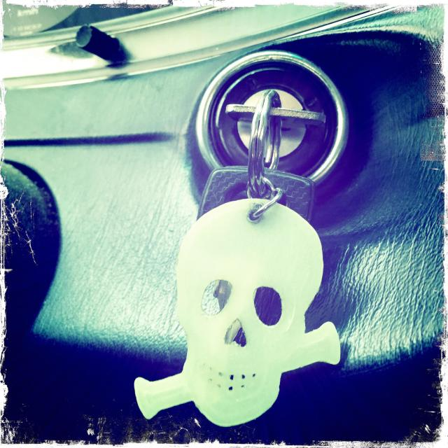 """Skull key holder on the board of a car"" stock image"