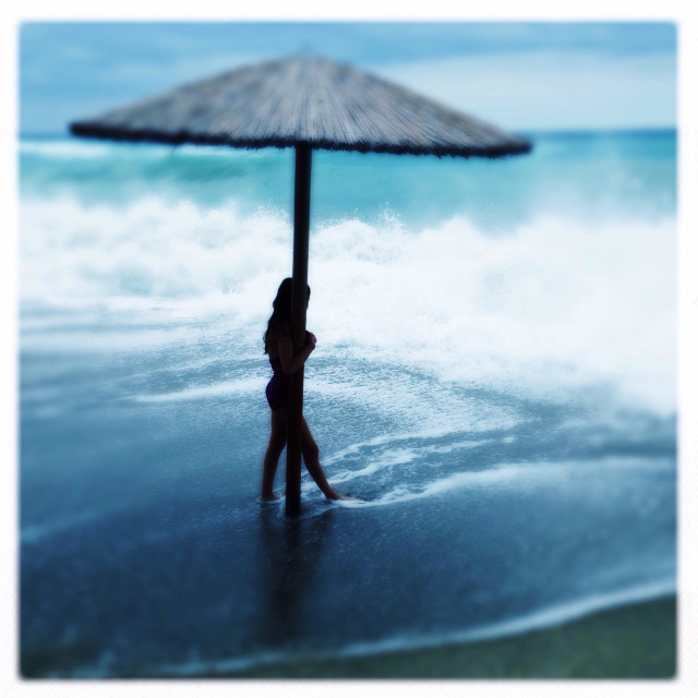 """Silouhette of girl holding on to a beach umbrella pole, standing on a dark sand beach with large white waves"" stock image"