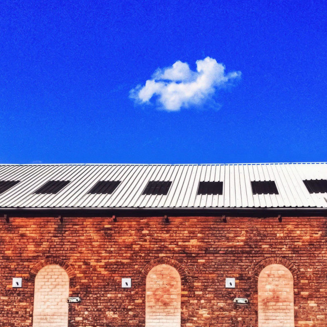 """Bricked up windows in brick wall against blue sky with single fluffy cloud"" stock image"