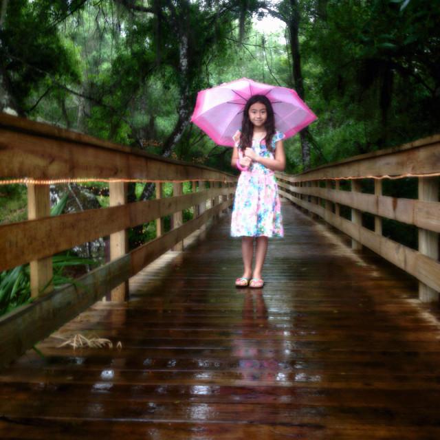 """Girl holding an umbrella."" stock image"