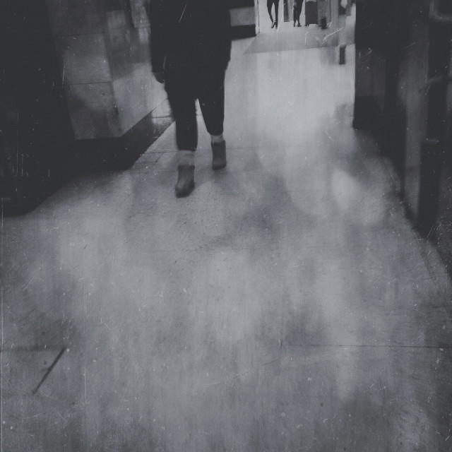 """""""Mysterious anonymous blurred hooded figure walking towards us in foggy mono style"""" stock image"""