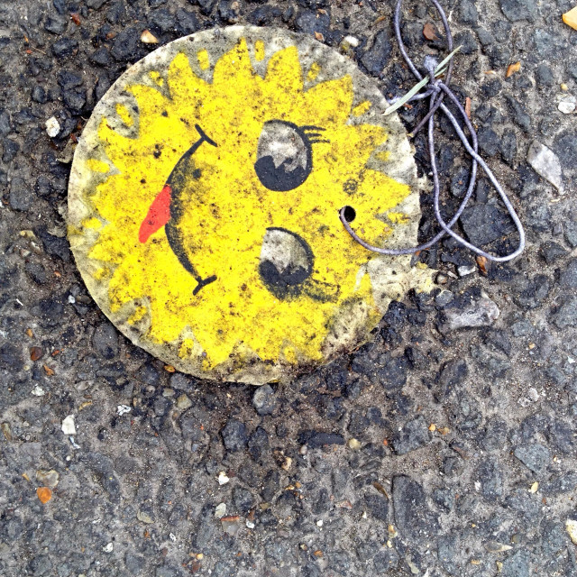 """A damaged and abandoned yellow metal smiley badge laying on the ground face up towards the viewer. Negative space for text on the right hand side."" stock image"