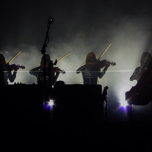 """Silhouette of the orchestra 'Dirty Pretty Strings' playing with Kasabian at Brixton Acadamy, UK, 4th December 2014."" stock image"