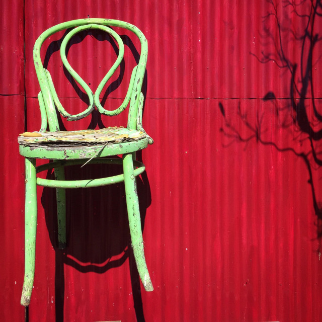 """Old light green chair attached to red corrugated iron shed door"" stock image"