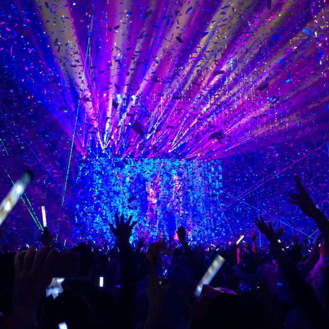"""""""Hands and glow sticks in the air as confetti rain down in a burst of color at the end of a concert."""" stock image"""