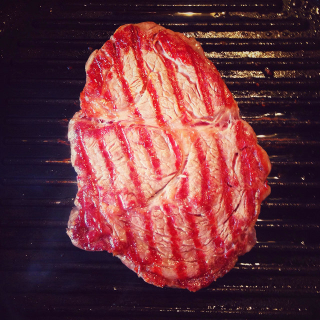 """Rib eye steak cooking on a griddle pan"" stock image"