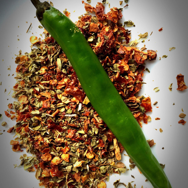 """A green chilli on a bed of chilli flakes and oregano."" stock image"