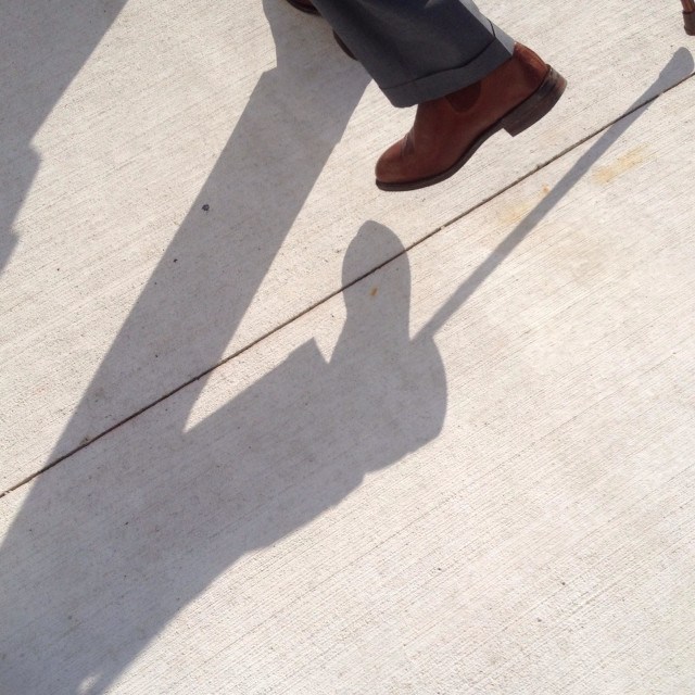 """Long shadow and feet of a gentleman with walking stick"" stock image"