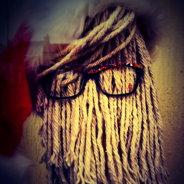 """A mop wearing specs and a Santa hat."" stock image"