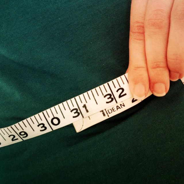 """Woman measuring her waist"" stock image"