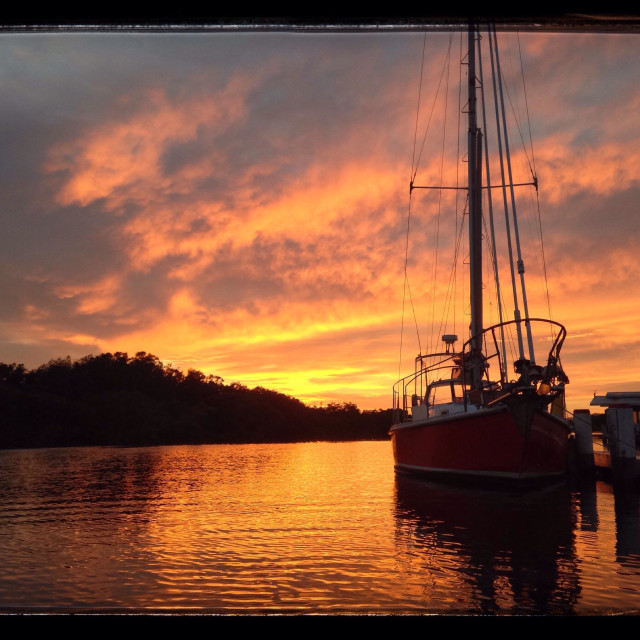 """Sailboat in front of orange sunrise in Woy Woy creek"" stock image"