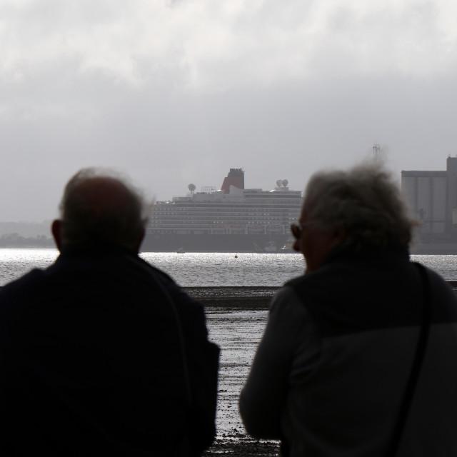 """Couple watching qm2 leaving Southampton water"" stock image"