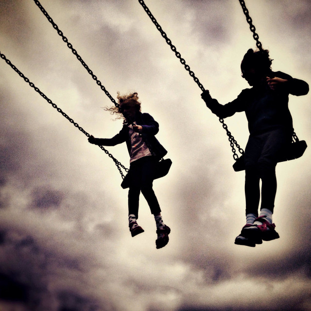 """""""Two girls on swings in silhouette against cloudy sky"""" stock image"""