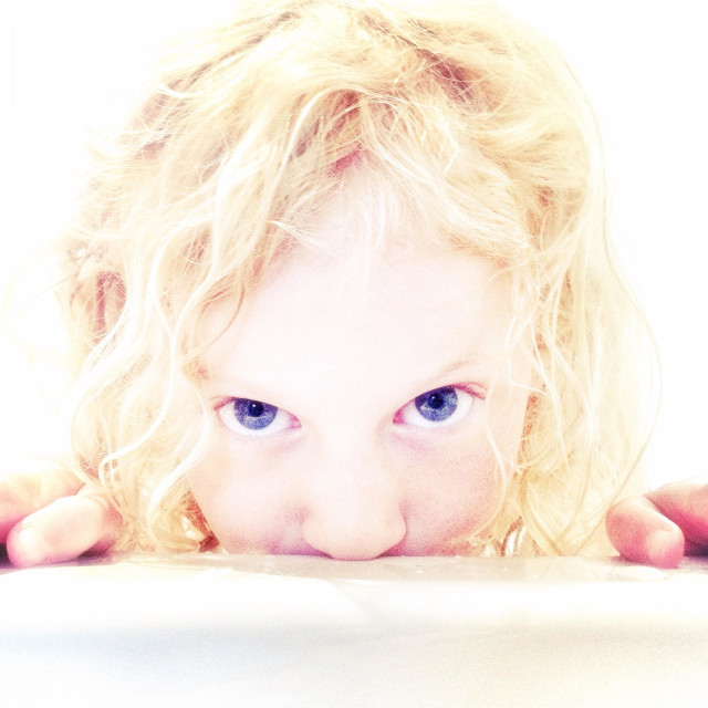 """""""Young blond girl looking over edge of bath"""" stock image"""