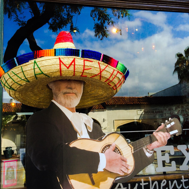 """""""Mexican restaurant lures customers with a cardboard guitar player on the sidewalk."""" stock image"""