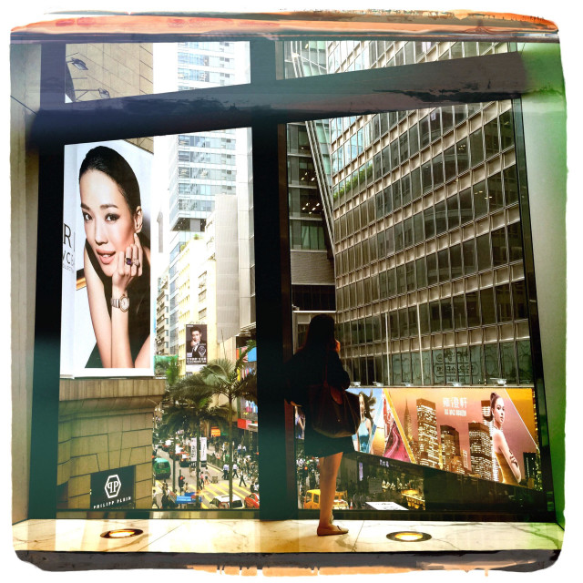 """Woman looking out of window towards street in Hong Kong"" stock image"