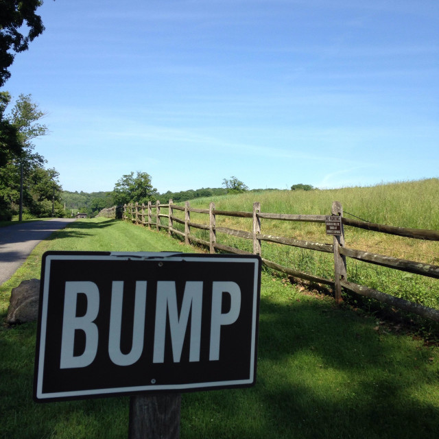 """""""A sign announcing """"Bump"""", on the side of a farm road."""" stock image"""