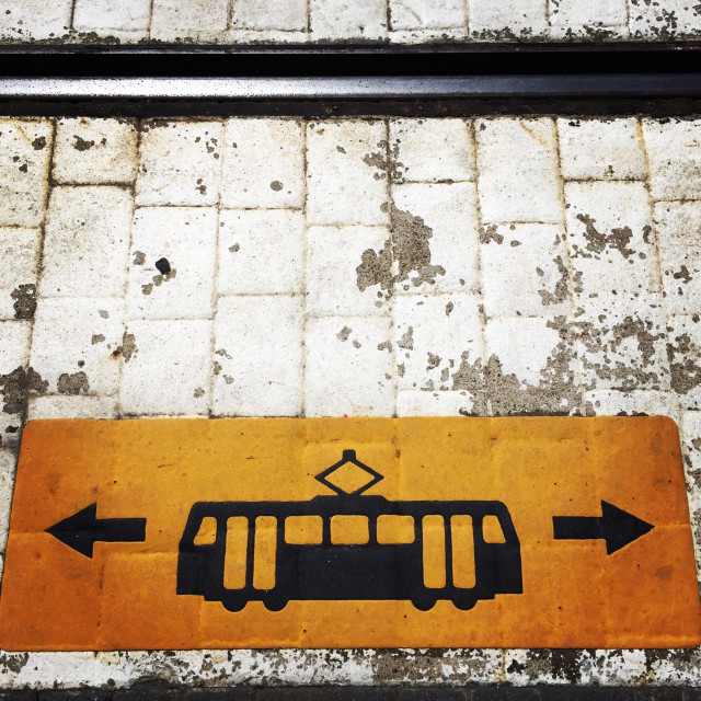 """""""Tram warning symbol painted on the ground beside tracks with directional arrows"""" stock image"""