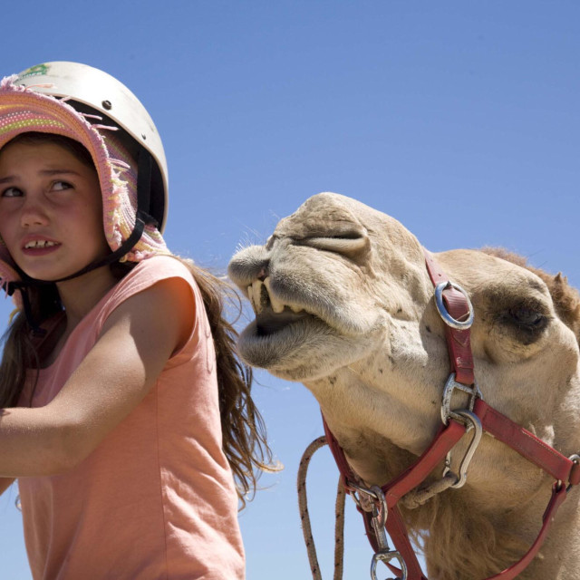 """""""Young girl worried whilst riding a camel"""" stock image"""
