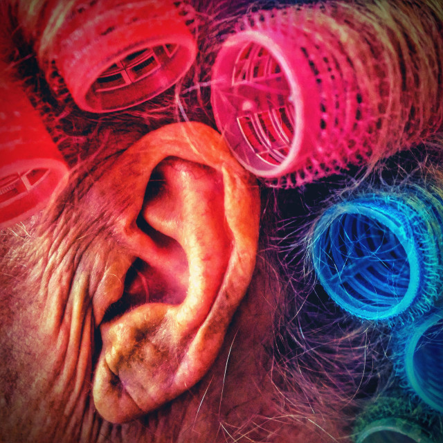 """""""Senior persons ear with coloured hair rollers"""" stock image"""