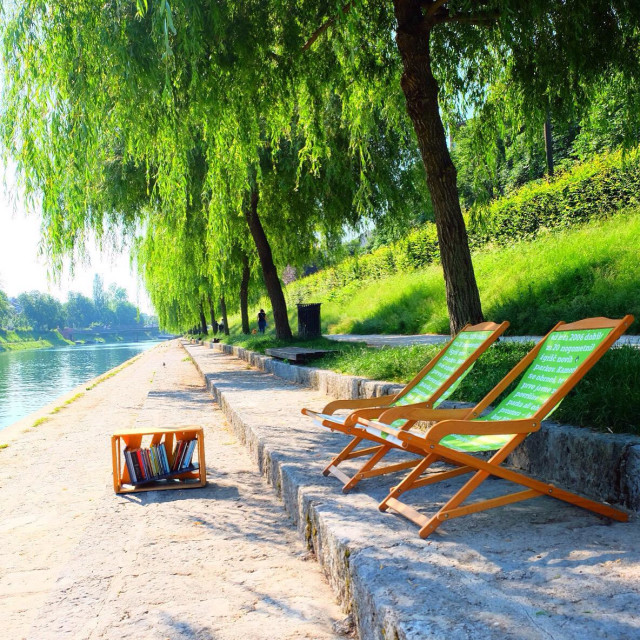 """""""Enjoying the peaceful moment in outdoor library by the river bank"""" stock image"""