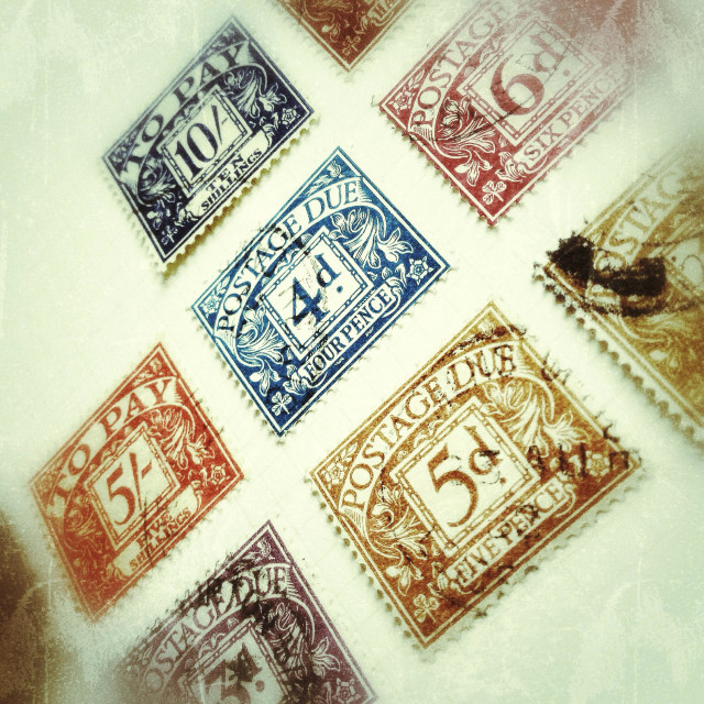 """Old postage due stamps in a stamp album."" stock image"