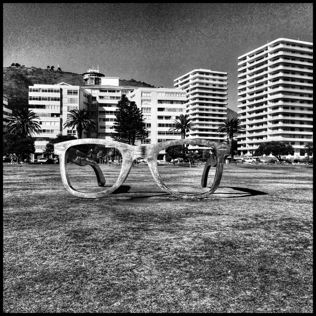 """""""Black and white photo of giant pair of Ray Bans that forms part of the interactive installation art along the Seapoint promenade ."""" stock image"""