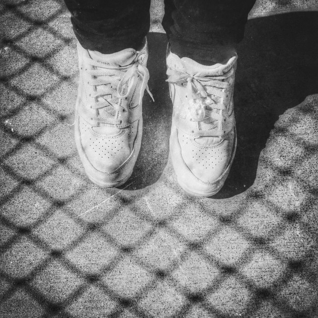 """""""White Sneakers Standing On Shadow Pattern From A Chain Link Fence"""" stock image"""