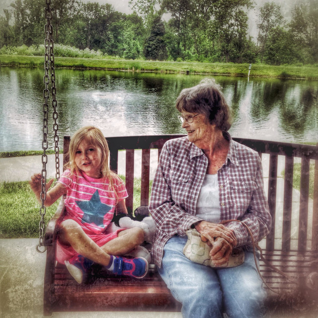 """A child sitting on a swing with her great grandmother."" stock image"