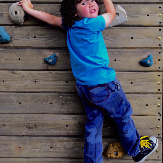 """Young boy 4 years old on climbing wall"" stock image"