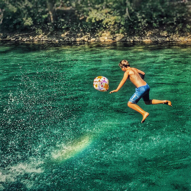 """""""A boy cools off by jumping into the Aare river, Berne, Switzerland"""" stock image"""