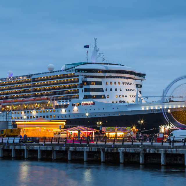 """""""Fairground rides in front of the Queen Mary Two."""" stock image"""