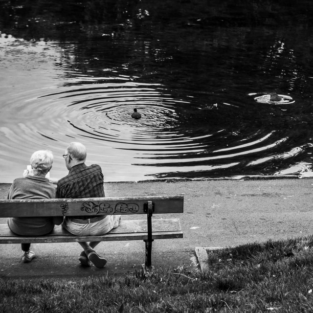 """Couple resting on a bench in Sefton Park"" stock image"