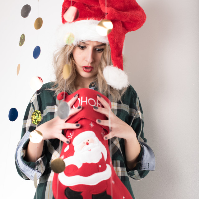 """surprised girl looking at Christmas sock"" stock image"