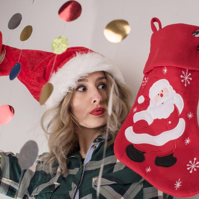 """young woman holding Christmas hat and Christmas sock"" stock image"
