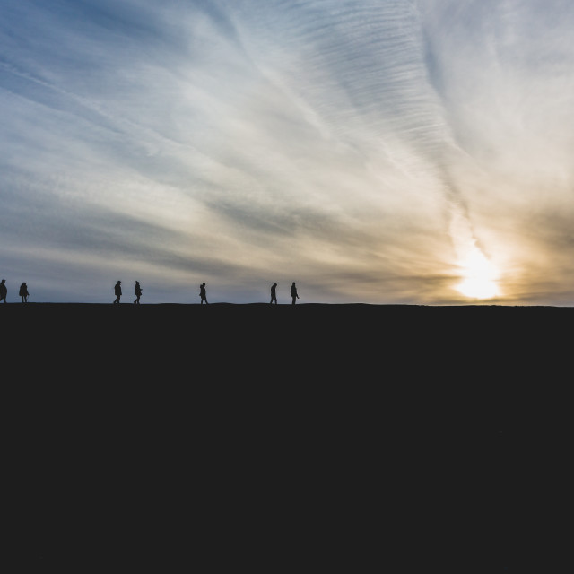 """People walk in sunset at cliffs edge"" stock image"