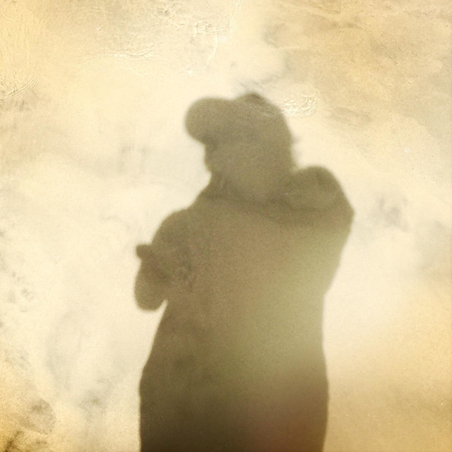 """""""A shadow of a male with a hat on at the beach."""" stock image"""