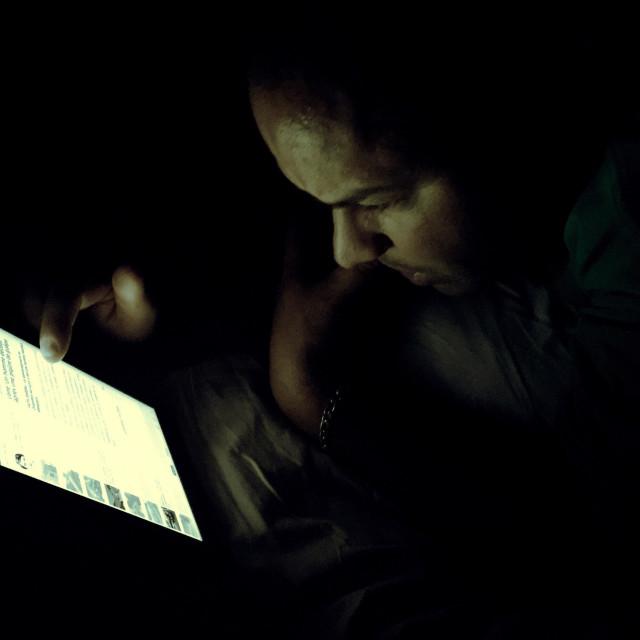 """Man reading on his iPad at night"" stock image"